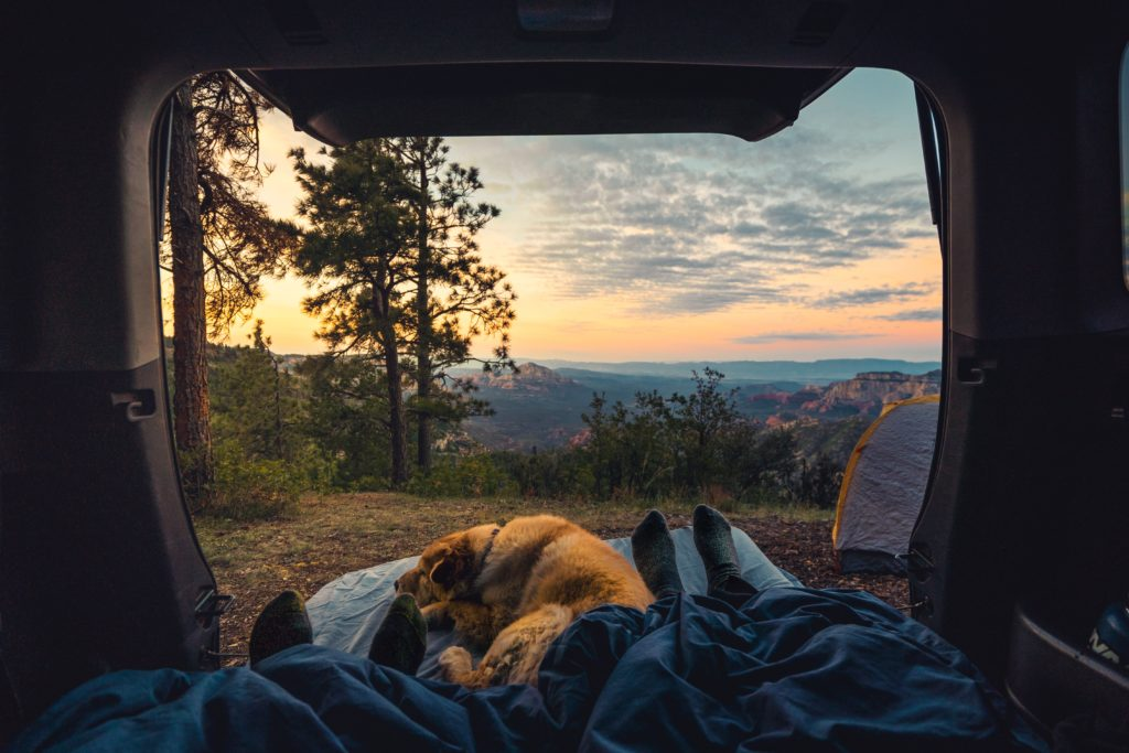 Enjoying sunrise while car camping over a cliff in Sedona, Arizona with girlfriend and dog.